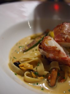 Roast monkfish tail wrapped in smoked bacon, roasted courgette, mussels, creamed tagliatelle
